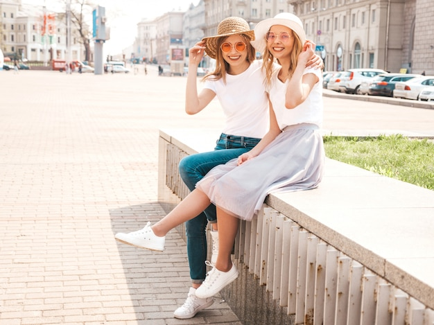 Twee jonge mooie blonde glimlachende hipster meisjes in trendy zomer wit t-shirt kleding. sexy onbezorgde vrouwen die op straatachtergrond zitten.