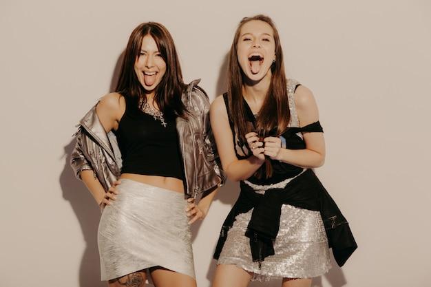 Twee jonge mooie blonde glimlachende hipster meisjes in trendy zomerkleren. sexy onbezorgde vrouwen die dichtbij muur in studio stellen positieve modellen die pret hebben