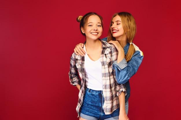 Twee jonge mooie blonde glimlachende hipster vrouwen die in trendy kleren van het de zomer geruite overhemd stellen