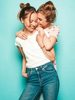 Twee jonge mooie blonde lachende hipster meisjes in trendy zomer hipster jeans kleding. sexy onbezorgde vrouwen die dichtbij blauwe muur stellen. trendy en positieve modellen die plezier hebben