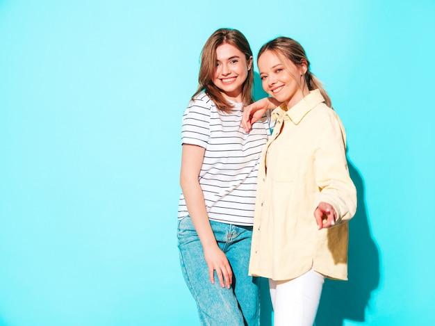 Twee jonge mooie blonde lachende hipster-vrouwen in trendy zomerkleding