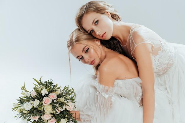 Twee jonge mooie bruiden poseren in trouwjurken met boeket rozen
