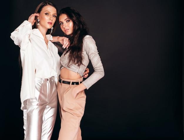 Twee jonge mooie brunette meisjes in mooie trendy zomer kleding