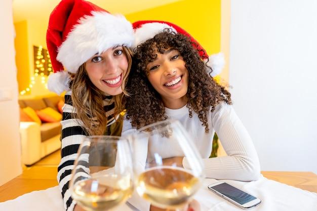 Twee jonge mooie gemengde rasvrouwen die kerstmanhoed dragen die de camera bekijken die witte wijnglazen houdt