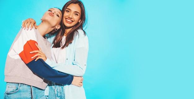 Twee jonge mooie glimlachende blonde hipstermeisjes in kleren van de trendy de zomer kleurrijke t-shirt. sexy onbezorgde vrouwen die dichtbij blauwe muur stellen. positieve modellen hebben plezier en maken eendgezicht