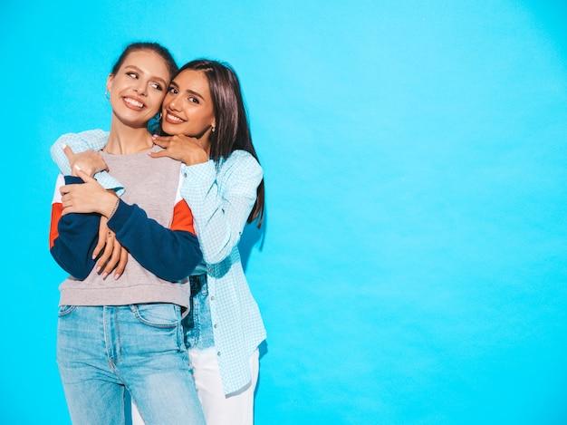 Twee jonge mooie glimlachende blonde hipstermeisjes in kleren van de trendy de zomer kleurrijke t-shirt. sexy onbezorgde vrouwen die dichtbij blauwe muur stellen. positieve modellen hebben plezier