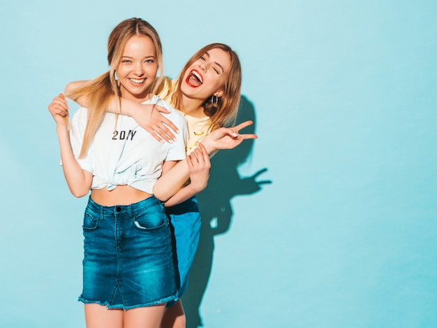 Twee jonge mooie glimlachende blonde hipstermeisjes in kleren van de trendy de zomer kleurrijke t-shirt.