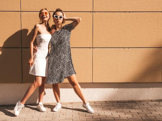 Twee jonge mooie glimlachende hipster meisjes in trendy zomer jurken.