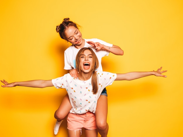 Twee jonge mooie glimlachende hipster meisjes in trendy zomerkleren. sexy onbezorgde vrouwen die dichtbij gele muur stellen. modelzitting op de rug van haar vriend en het opheffen van handen