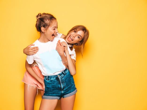 Twee jonge mooie glimlachende hipster meisjes in trendy zomerkleren. sexy onbezorgde vrouwen die dichtbij gele muur stellen. positieve modellen worden gek en hebben plezier