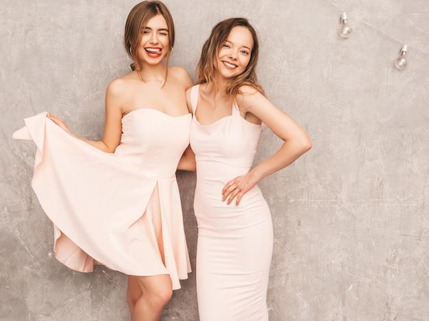 Twee jonge mooie glimlachende meisjes in trendy zomer lichtroze jurken. sexy zorgeloze vrouwen poseren. positieve modellen hebben plezier