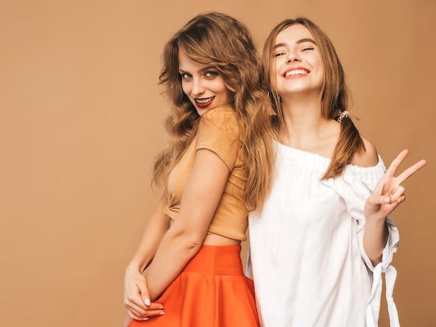 Twee jonge mooie glimlachende meisjes in trendy zomerkleren. sexy zorgeloze vrouwen poseren. positieve modellen die vredesteken tonen
