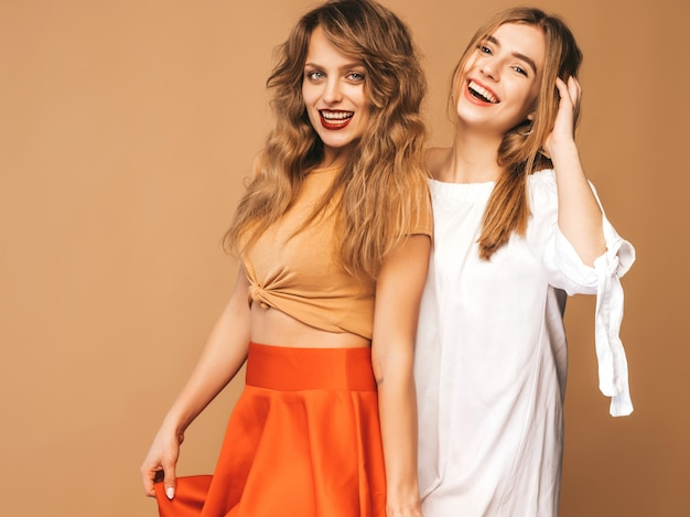 Twee jonge mooie glimlachende meisjes in trendy zomerkleren. sexy zorgeloze vrouwen poseren. positieve modellen
