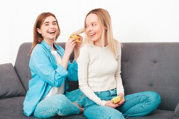 Twee jonge mooie glimlachende vrouwen die bij de bank zitten