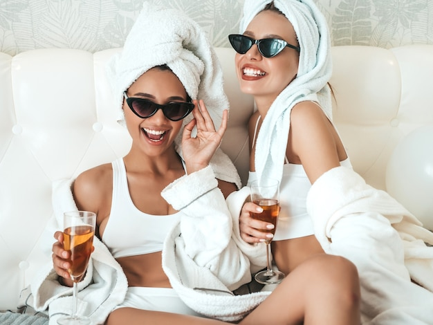 Twee jonge mooie glimlachende vrouwen in witte badjassen en handdoeken op het hoofd