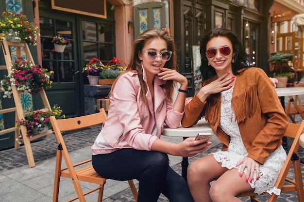 Twee jonge mooie hipster vrouwen zitten in café
