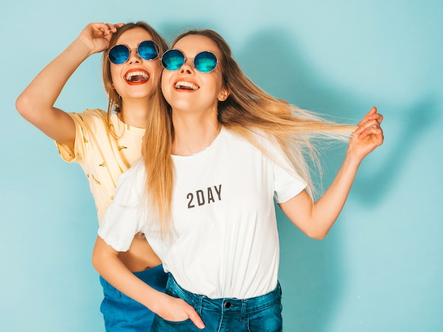Twee jonge mooie lachende blonde hipster meisjes in trendy zomer jeans rokken kleding.
