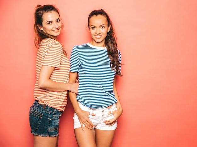 Twee jonge mooie lachende brunette hipster meisjes in trendy soortgelijke gestreepte zomer kleurrijke shirt kleding. sexy zorgeloze vrouwen poseren in de buurt van roze muur in de studio. positieve modellen plezier