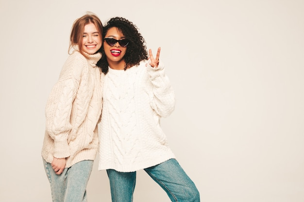 Twee jonge mooie lachende hipster meisjes in trendy winter truien. positieve modellen die plezier hebben en knuffelen