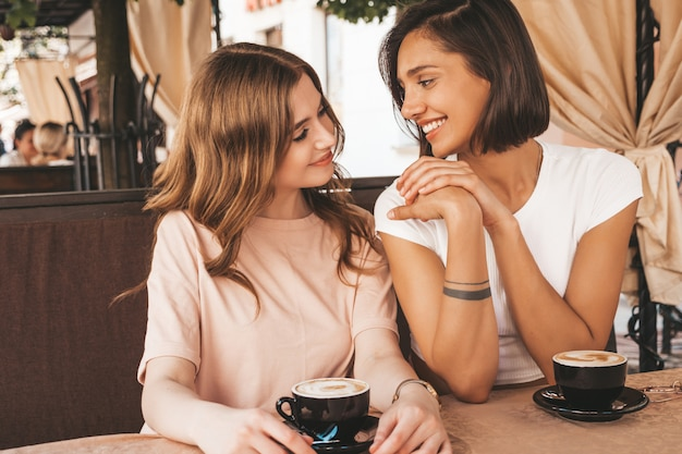 Twee jonge mooie lachende hipster meisjes in trendy zomer casual kleding. zorgeloze vrouwen chatten in veranda terras cafe en koffie drinken. positieve modellen met plezier en communiceren