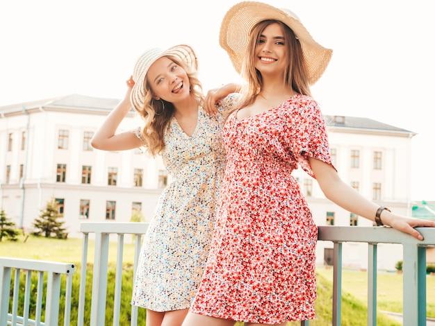 Twee jonge mooie lachende hipster meisjes in trendy zomer sundress. sexy zorgeloze vrouwen die zich voordeed op de straat achtergrond in hoeden. positieve modellen die plezier hebben en knuffelen