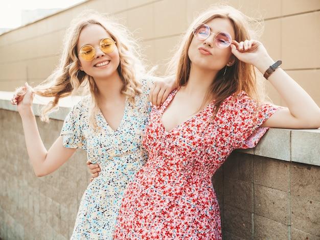 Twee jonge mooie lachende hipster meisjes in trendy zomer sundress. sexy zorgeloze vrouwen die zich voordeed op de straat achtergrond in zonnebril. positieve modellen die plezier hebben en knuffelen