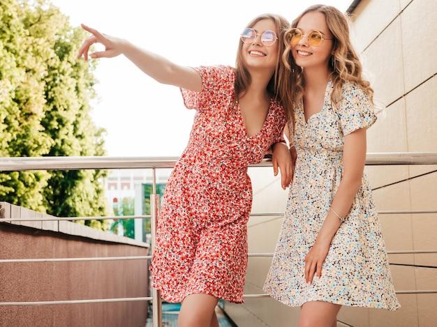 Twee jonge mooie lachende hipster meisjes in trendy zomer sundress. sexy zorgeloze vrouwen die zich voordeed op de straat achtergrond in zonnebril. positieve modellen die plezier hebben en op iets interessants wijzen