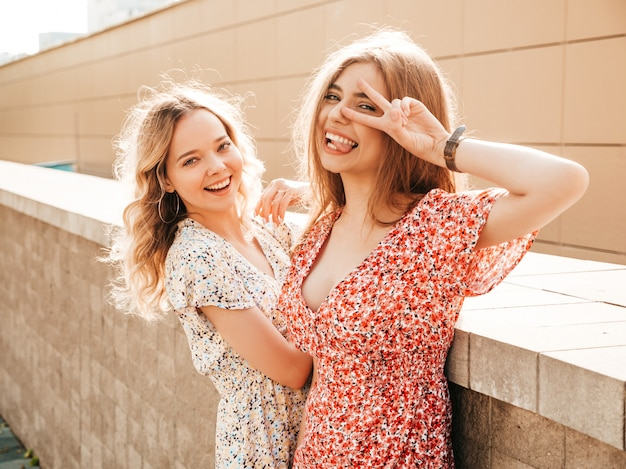 Twee jonge mooie lachende hipster meisjes in trendy zomer sundress. sexy zorgeloze vrouwen die zich voordeed op de straat achtergrond. positieve modellen die pret hebben en vredesteken tonen