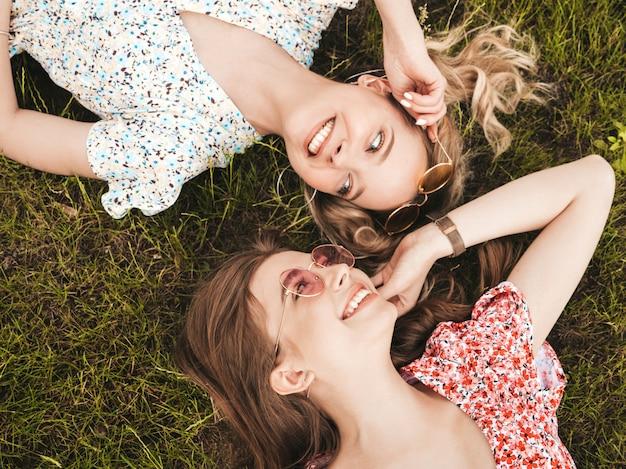 Twee jonge mooie lachende hipster meisjes in trendy zomer sundress. sexy zorgeloze vrouwen liggend op het groene gras in zonnebril. positieve modellen met plezier. bovenaanzicht