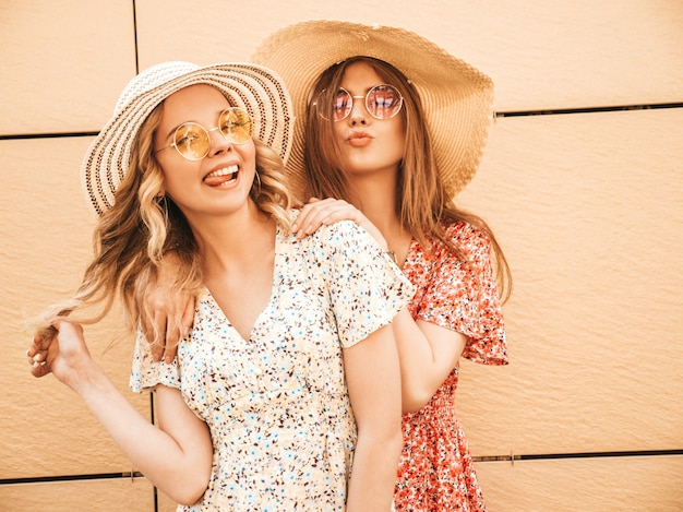 Twee jonge mooie lachende hipster meisjes in trendy zomer sundress. sexy zorgeloze vrouwen poseren in de buurt van muur in de straat in zonnebril. positieve modellen die plezier hebben en knuffelen in hoeden.toon tong