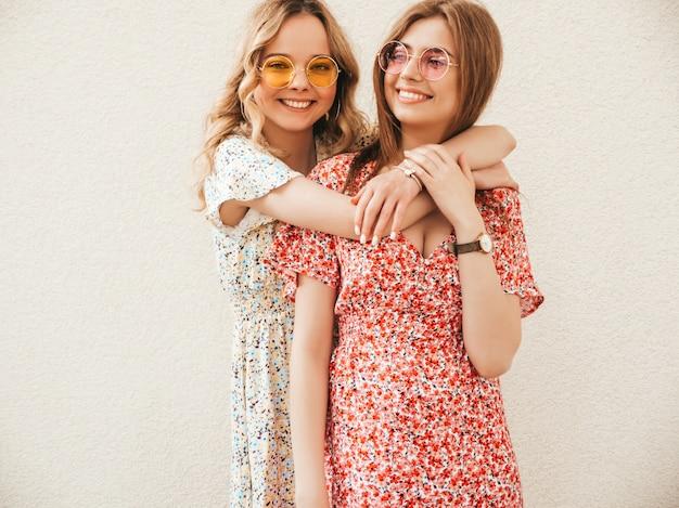 Twee jonge mooie lachende hipster meisjes in trendy zomer sundress. sexy zorgeloze vrouwen poseren in de buurt van muur op straat achtergrond in zonnebril. positieve modellen die plezier hebben en knuffelen