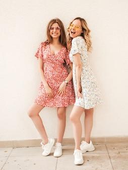Twee jonge mooie lachende hipster meisjes in trendy zomer sundress. sexy zorgeloze vrouwen poseren in de buurt van muur op straat in zonnebril. positieve modellen die plezier hebben en knuffelen
