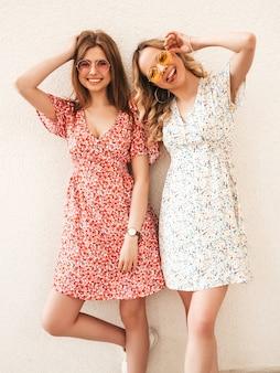 Twee jonge mooie lachende hipster meisjes in trendy zomer sundress. sexy zorgeloze vrouwen poseren in de straat in de buurt van muur in zonnebril. positieve modellen die plezier hebben en gek worden