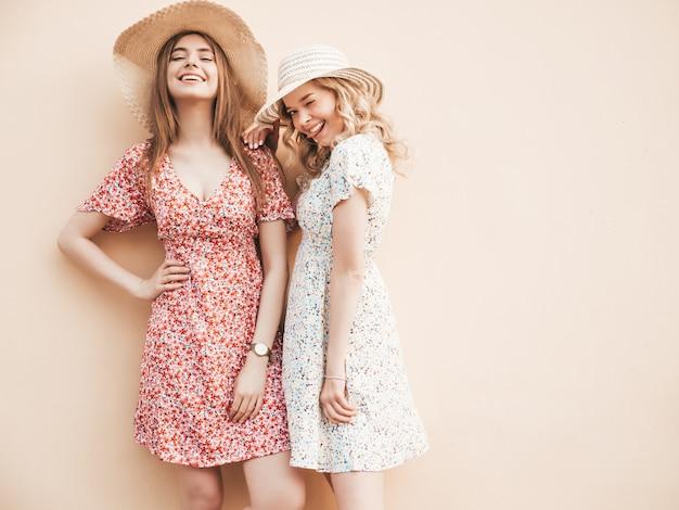 Twee jonge mooie lachende hipster meisjes in trendy zomer sundress. sexy zorgeloze vrouwen poseren op straat in de buurt van muur in hoeden. positieve modellen die plezier hebben en knuffelen