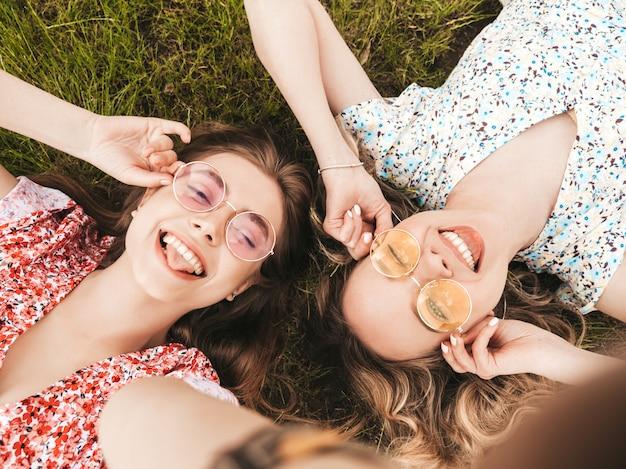 Twee jonge mooie lachende hipster meisjes in trendy zomer zonnejurk. sexy zorgeloze vrouwen liggend op het groene gras in zonnebril. positieve modellen plezier. bovenaanzicht. selfie foto's maken op smartphone