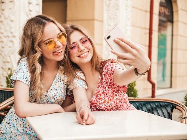 Twee jonge mooie lachende hipster meisjes in trendy zomer zonnejurk. zorgeloze vrouwen chatten in veranda cafe op de straat achtergrond. positieve modellen met plezier en nemen selfie op smartphone