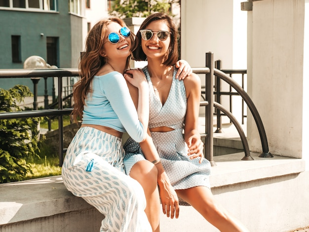 Twee jonge mooie lachende hipster meisjes in trendy zomerkleding. sexy zorgeloze vrouwen die zich voordeed op de straat achtergrond in zonnebril. positieve modellen die plezier hebben en gek worden