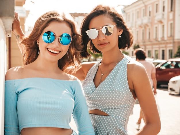 Twee jonge mooie lachende hipster meisjes in trendy zomerkleding. sexy zorgeloze vrouwen die zich voordeed op straat achtergrond in zonnebril. positieve modellen die plezier hebben en knuffelen