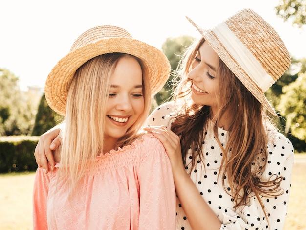 Twee jonge mooie lachende hipster vrouw in trendy zomer zomerjurk. sexy zorgeloze vrouwen poseren in het park in hoeden.