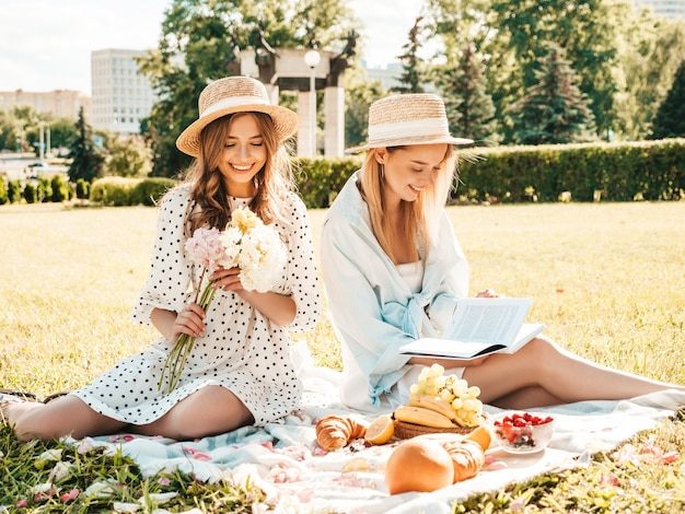 Twee jonge mooie lachende hipster vrouw in trendy zomerjurk en hoeden. zorgeloze vrouwen die picknick maken.