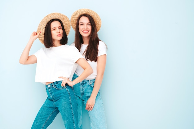 Twee jonge mooie lachende hipster-vrouwen in trendy dezelfde zomer witte t-shirt en jeans kleding
