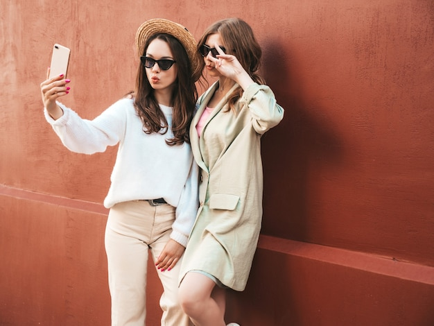Twee jonge mooie lachende hipster-vrouwen in trendy witte trui en jas