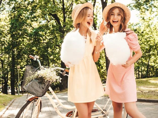 Twee jonge mooie lachende hipster-vrouwen in trendy zomerjurk