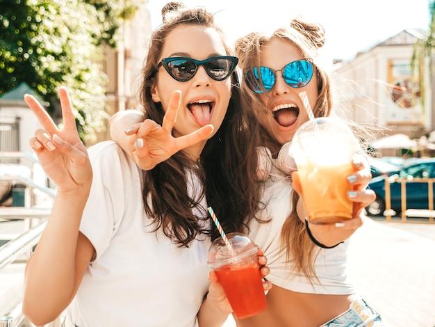 Twee jonge mooie lachende hipster-vrouwen in trendy zomerkleding