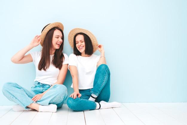 Twee jonge mooie lachende hipster-vrouwen in trendy zomers wit t-shirt en jeanskleding