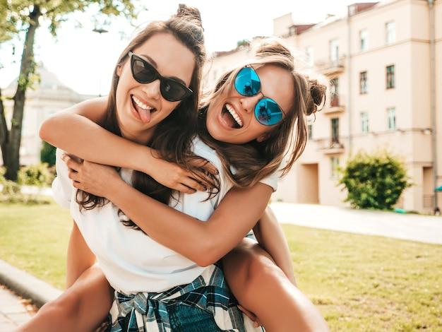 Twee jonge mooie lachende hipster-vrouwen in trendy zomerse witte t-shirtkleren