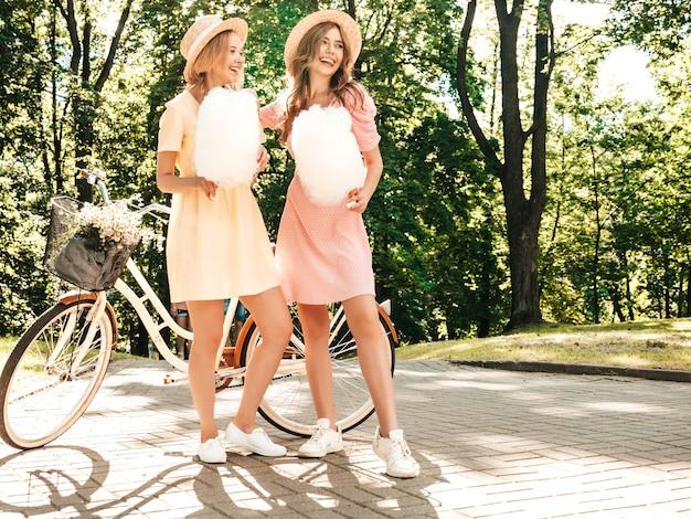 Twee jonge mooie lachende hipstermeisjes in trendy zomerjurk