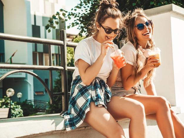 Twee jonge mooie lachende hipstermeisjes in trendy zomerkleren