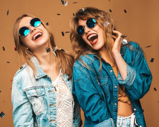 Twee jonge mooie lachende meisjes in trendy zomer kleding en zonnebril. sexy zorgeloze vrouwen poseren. positieve schreeuwende modellen onder confetti