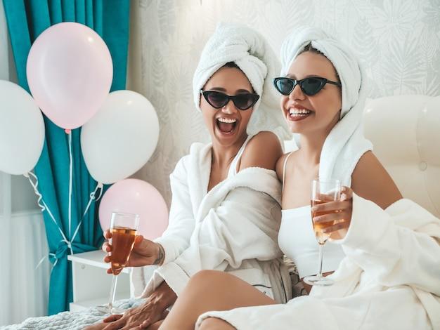 Twee jonge mooie lachende meisjes in witte badjassen en handdoeken op het hoofd
